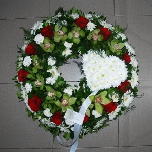 Coroa fúnebre aberta em tons verdes, brancos e vermelho com um coração em margaridas brancas